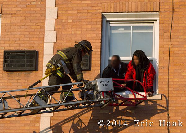 firemen rescue resident via ladder out the window of apartment building