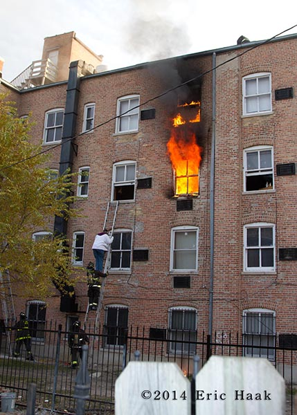 firemen rescue resident via ladder as fire blows out the window of apartment building