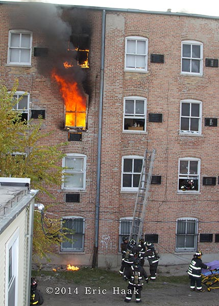 fire blows out the window of apartment building