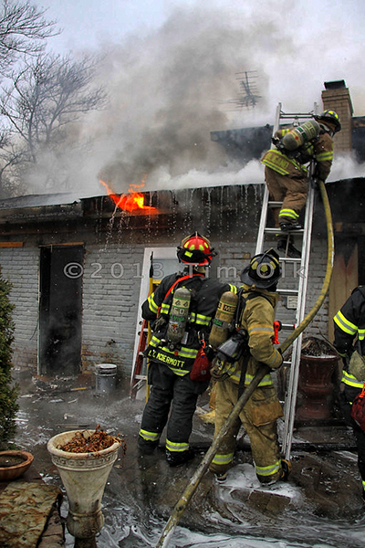 firefighters with hose line on ladder at house fire