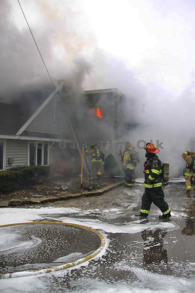 firemen at house fire scene with heavy smoke