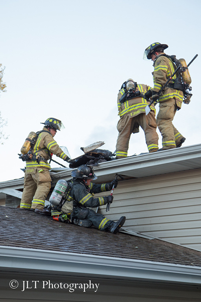 firemen doing overhaul on soffit