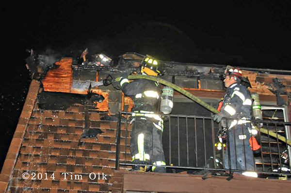 firemen on balcony with hose at night with mansard roof