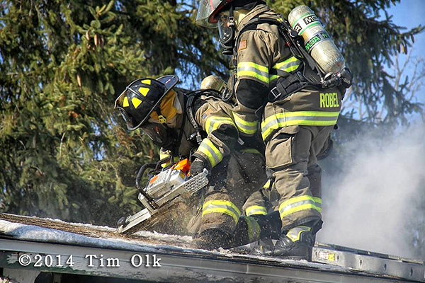 firemen cutting into roof of a house