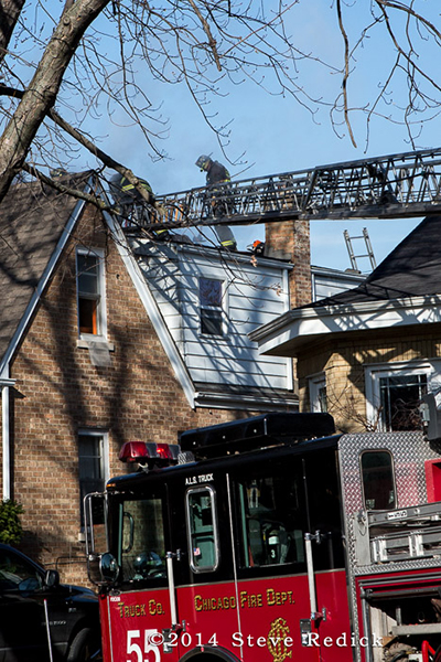 firemen with aerial ladder to the roof of a house