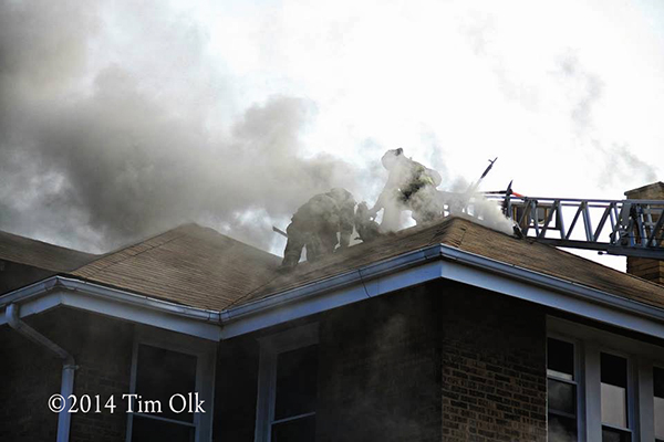 firemen vent roof in smoke