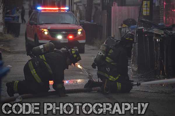 firemen in alley with hose line