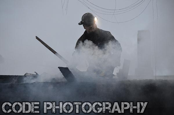 fireman on roof with smoke