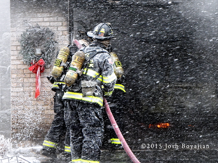 firemen operate hose in snow storm