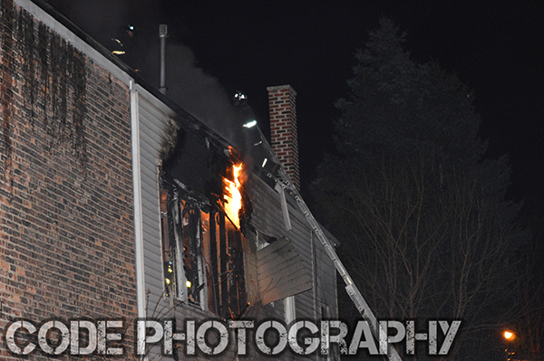 fireman on ladder at night with fire