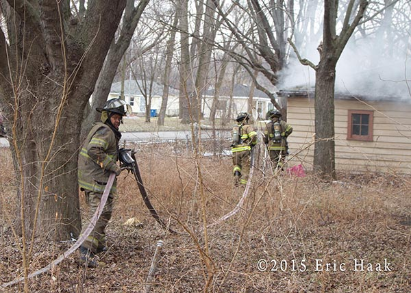 firemen stretch a line on a vacant house fire