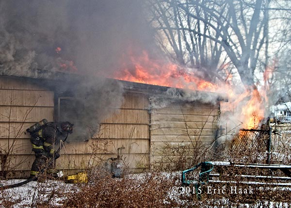 fireman stretching a line on a vacant house fire
