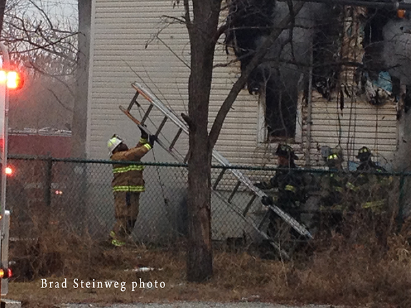 firemen maneuver ladder at fire scene