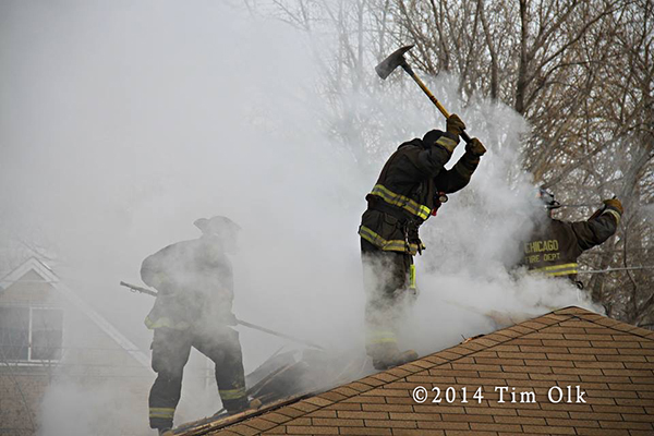 firemen in smoke on roof of house during a fire