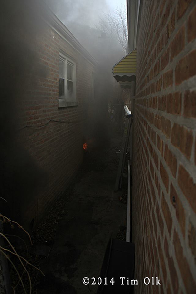 narrow gangway between homes with one on fire