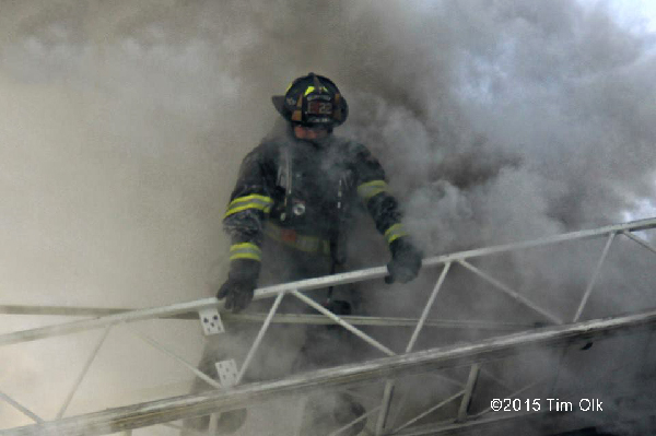 fireman on aerial ladder with smoke
