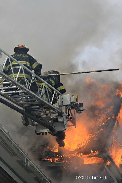 firemen on ladder tip with fire