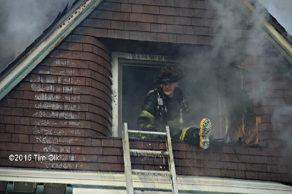 fireman in window overhauling house after fire