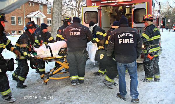 an injured firefighter is rushed to an ambulance