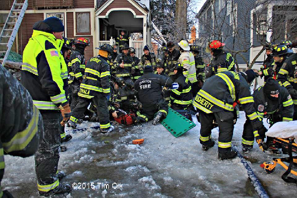 firemen aid a fellow firefighter that was injured at a house fire