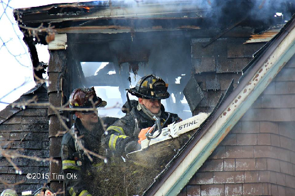firemen in window overhauling house after fire