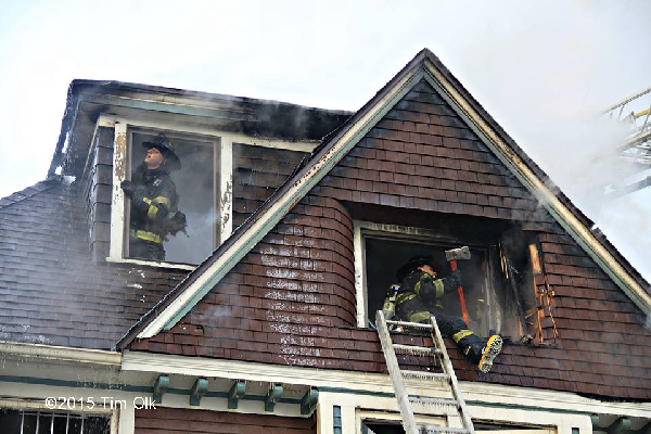 firemen in window overhauling house after fire