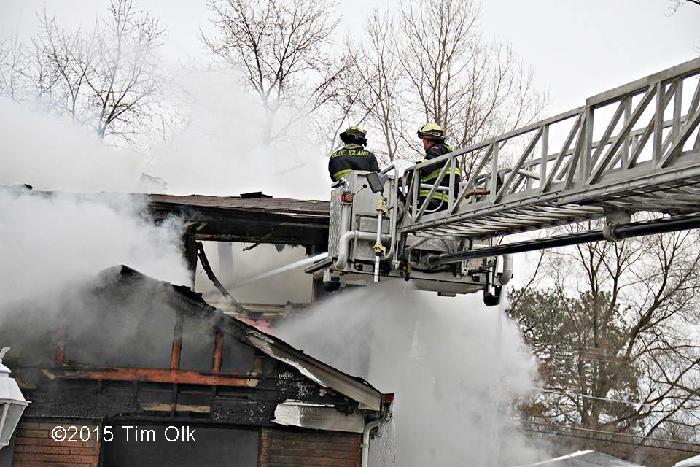 firemen in tower ladder at house fire