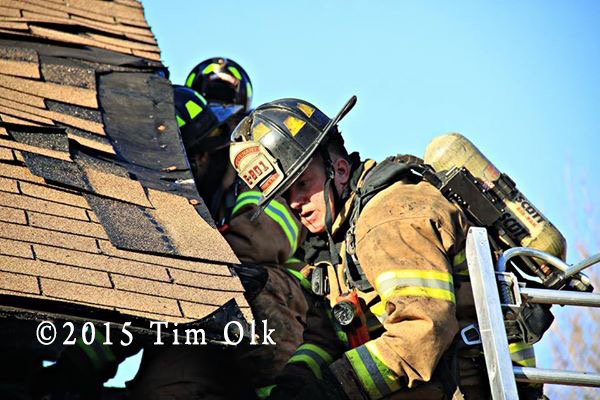 fireman on roof doing overhaul