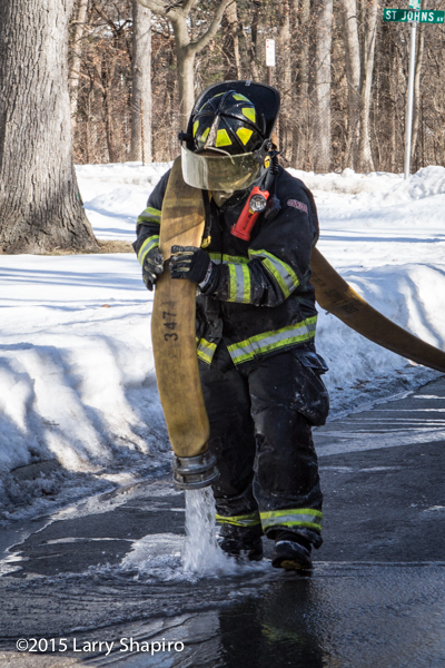 fireman drainign large diameter hose in the winter