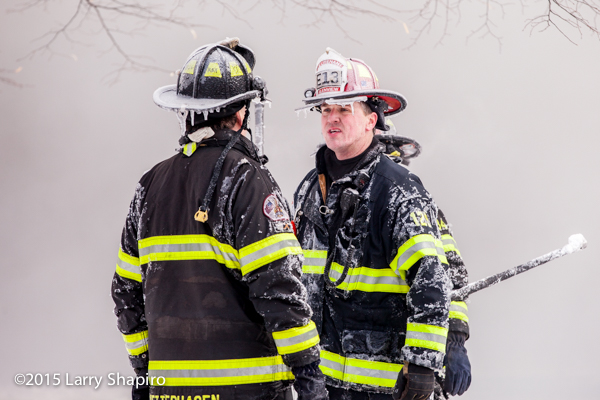 firemen coated with ice at fire scene