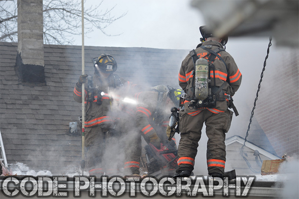 firemen on roof with saws and smoke