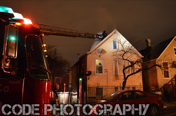 fire department ladder truck to roof of house at night