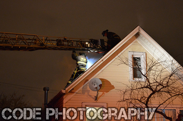 firemen on roof at house fire at night
