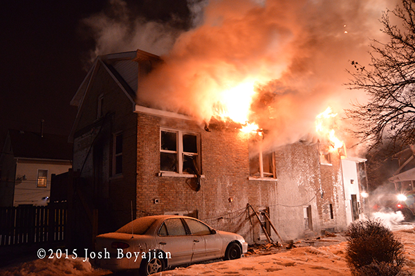 flames through the roof of a house at night in the winter