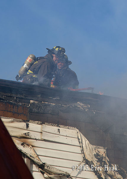 firemen overhaul roof after fire