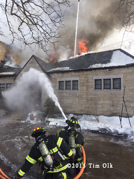 firemen with hose line at winter fire