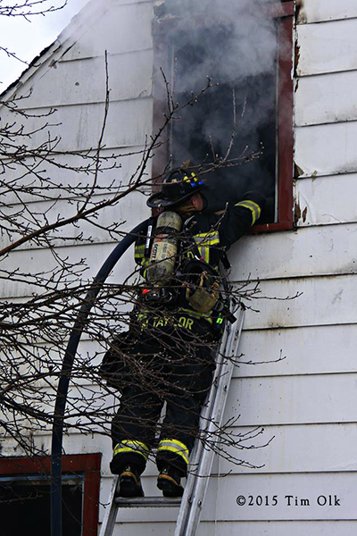 fireman with hose on ladder