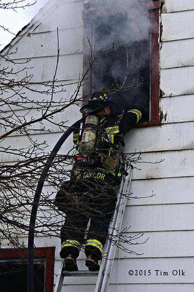 fireman with hose on ladder