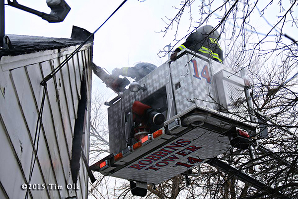 firemen in tower ladder platform at fire scene