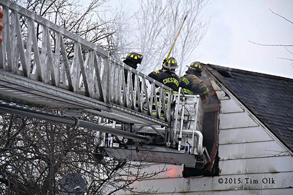 firemen in tower ladder platform at fire scene