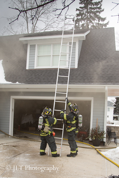 firemen raise a ground ladder