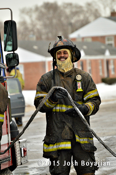 soaking wet fireman with hose after battling a fire