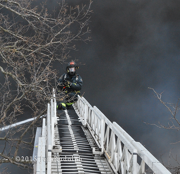 fireman on aerial ladder with black sky