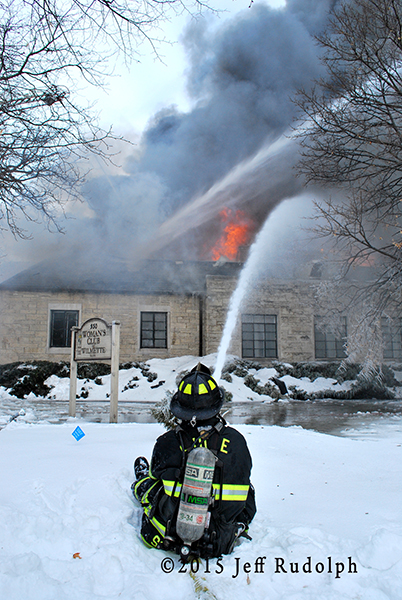 fireman with hose line at winter fire scene