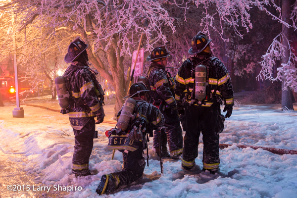 firemen covered with ice at winter fire scene