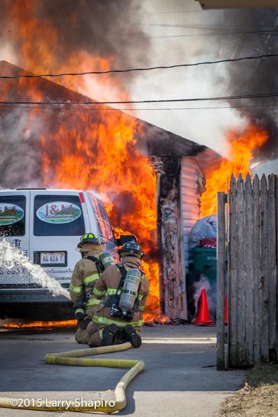 firemen with hose battle garage fire