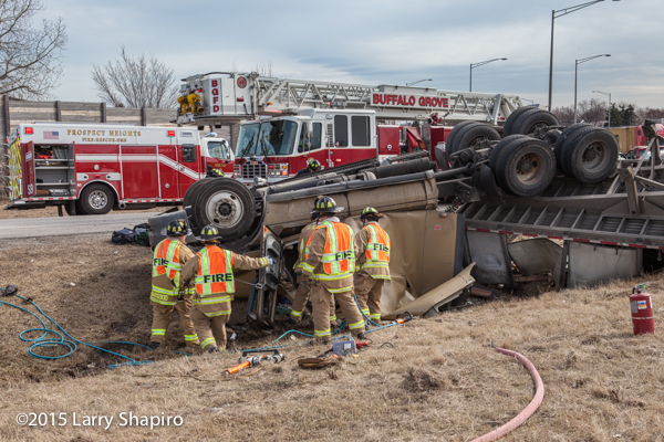 firemen cut victim from rolled over semi tractor