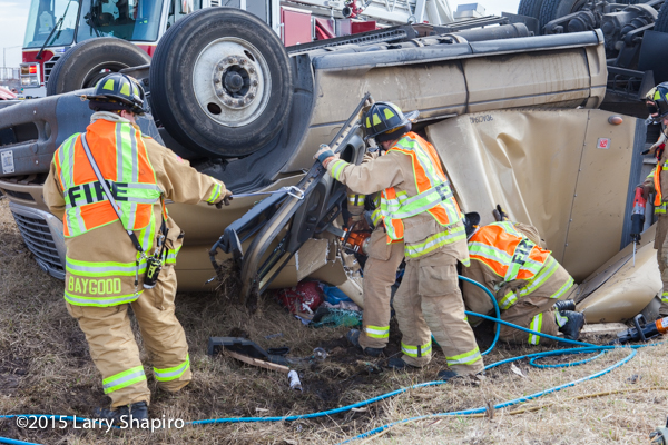 firemen rescue victim from rolled over semi tractor