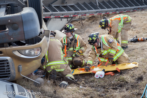 firemen remove victim from rolled over semi tractor