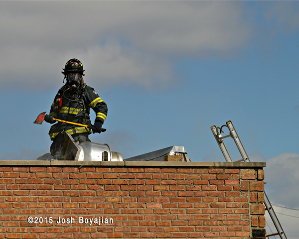 firemen on roof at commercial fire
